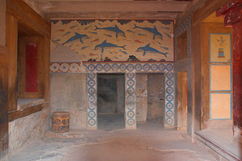 Room with dolphin frescoes and decorated walls and pillars.